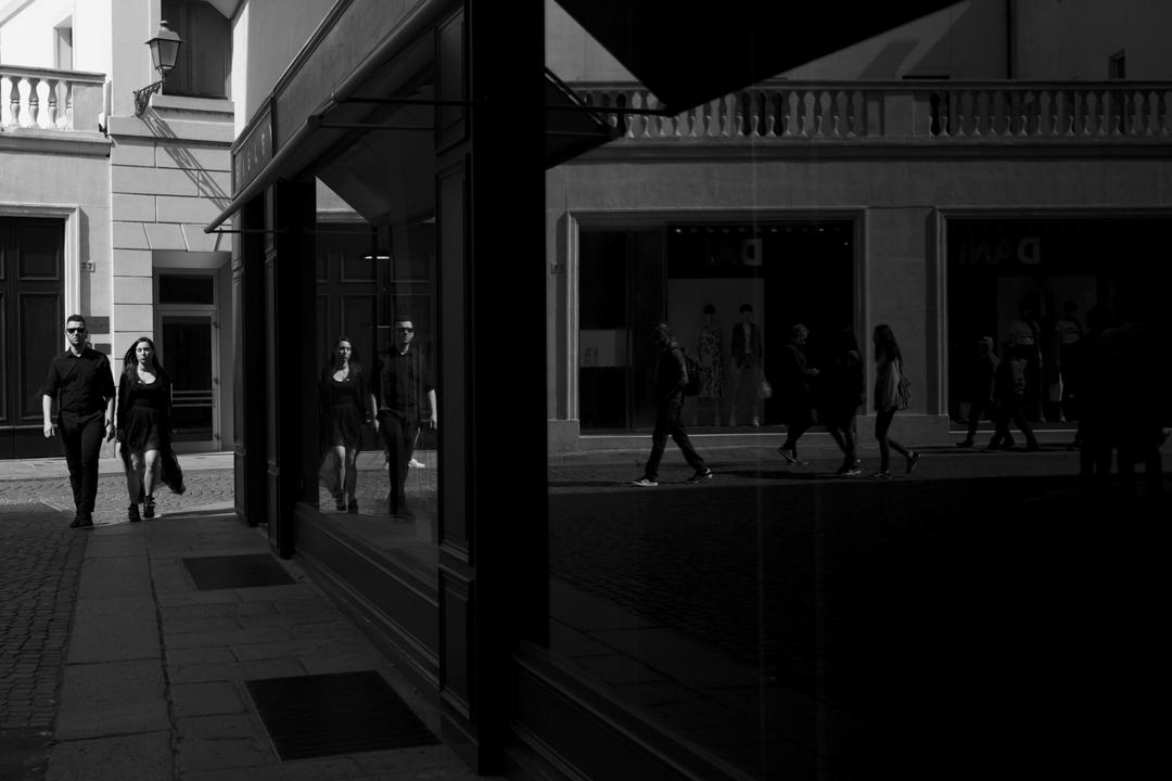 Coppia cammina per strada, riflesso su vetrina di negozio. Servizio fotografico di coppia SWP a Vicenza