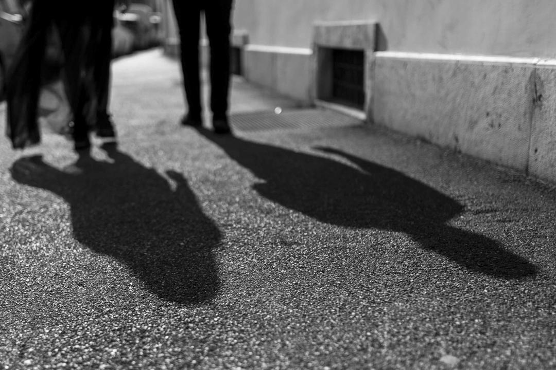La coppia cammina per la strada, le ombre si allungano sull'asfalto. Servizio fotografico di coppia SWP a Vicenza