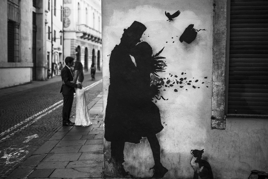 Promessa di matrimonio a Padova. Servizio SWP. Foto di coppia che si bacia sullo sfondo, murales in primo piano